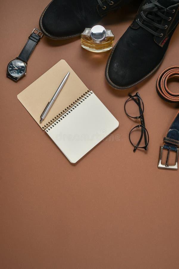 Модель-макет дня отцов с ручкой, духами, поясом, обувью, блокнотом и eyeglasses на коричневой предпосылке Установите стильных муж стоковое фото rf