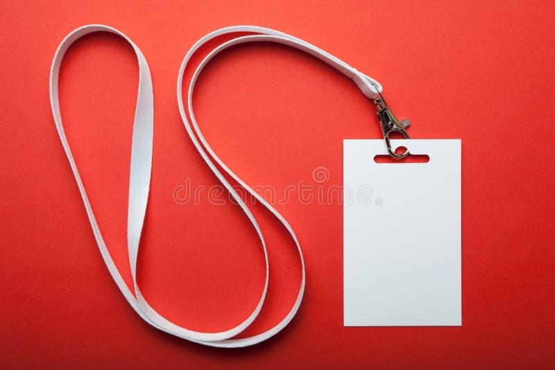 Модель-макет значка пробела белый вертикальный, изолированный на красной предпосылке Бирка имени на шеи Ярлык идентичности челове стоковые фотографии rf