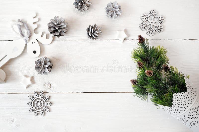 Модель-макет рождества на белой деревянной предпосылке с снежинками, оленем и рождественской елкой Плоское положение, взгляд свер стоковые изображения