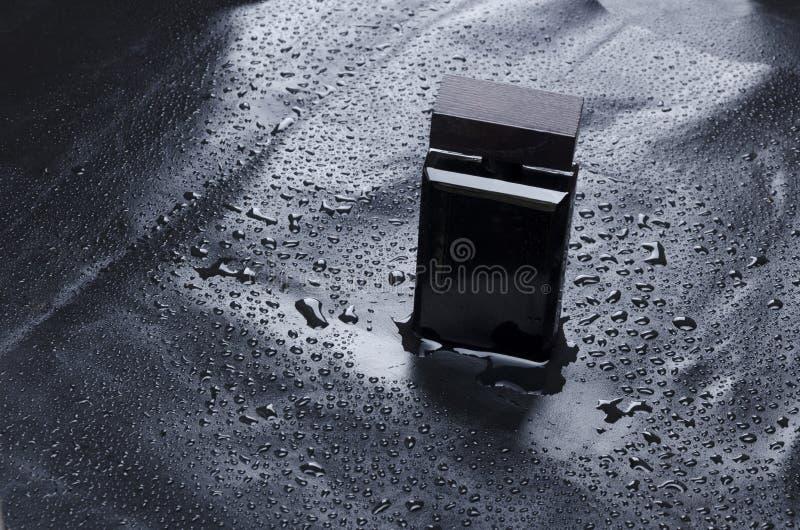 Модель-макет элегантной бутылки духов на воде падает предпосылка Концепция тонов moonlignt стоковое изображение