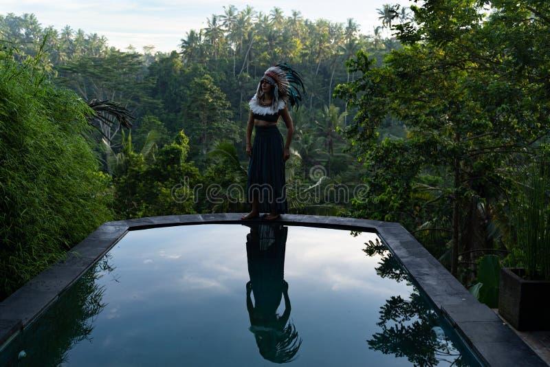Модель одетая в американском индейце представляя на крае пейзажного бассейна в джунглях на восходе солнца стоковое изображение