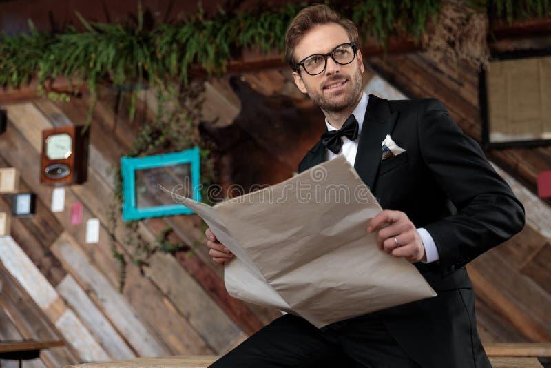 модель пенсивной моды, держащая газету и отводя взгляд стоковая фотография rf
