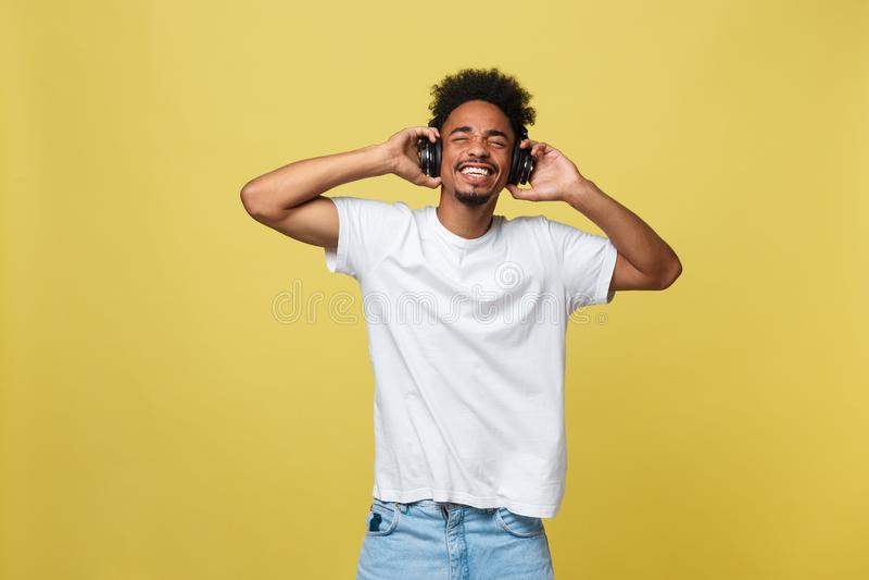 Модель портрета симпатичная африканская мужская при борода слушая к музыке Изолированный над желтой предпосылкой стоковое изображение