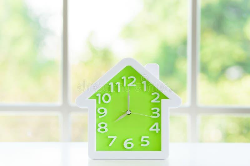 Модель часов с 8 a M и предпосылка окна в утре стоковая фотография