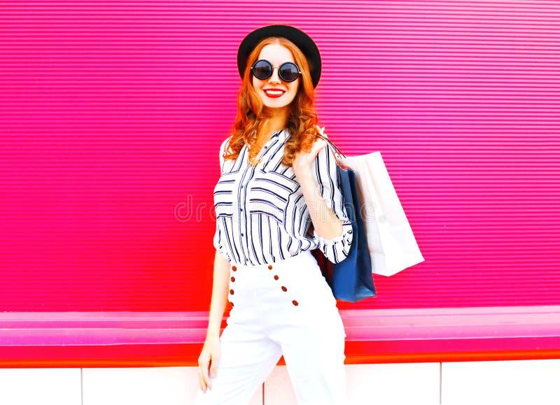 Модель элегантной женщины при хозяйственные сумки нося черную шляпу стоковые фото