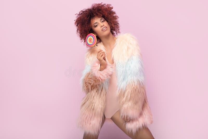 Модная афро женщина с леденцом на палочке на розовой предпосылке стоковые изображения rf
