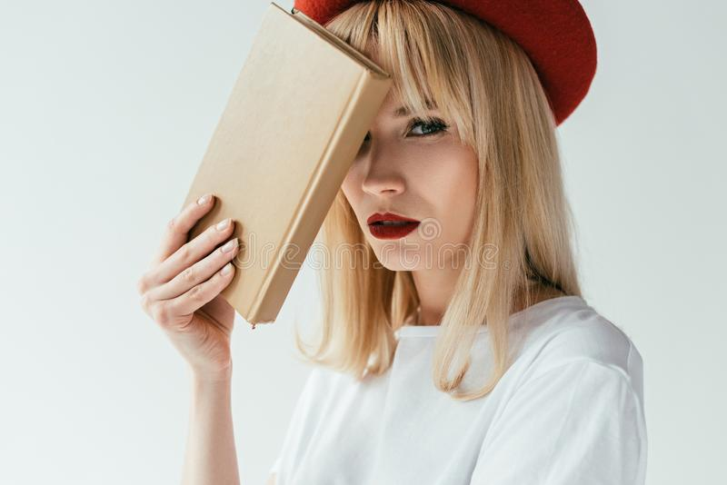 Модная белокурая девушка с красными губами держа книгу стоковая фотография