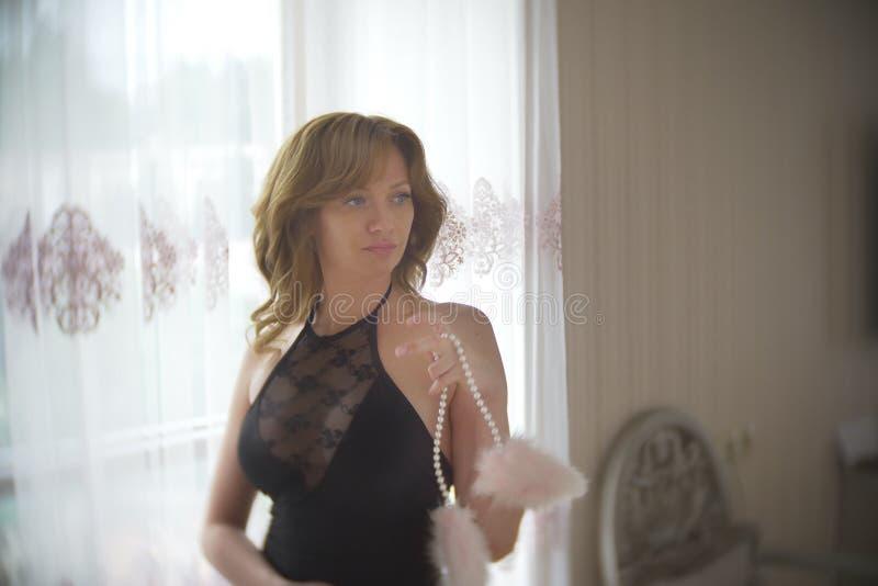Модная дама одела в выравнивать черное платье шнурка Молодая женщина представляя в чувственном представлении держа розовые пушист стоковое фото