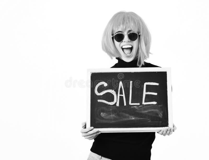 Модная девушка в доске удерживания парика с надписью продажи стоковые фото