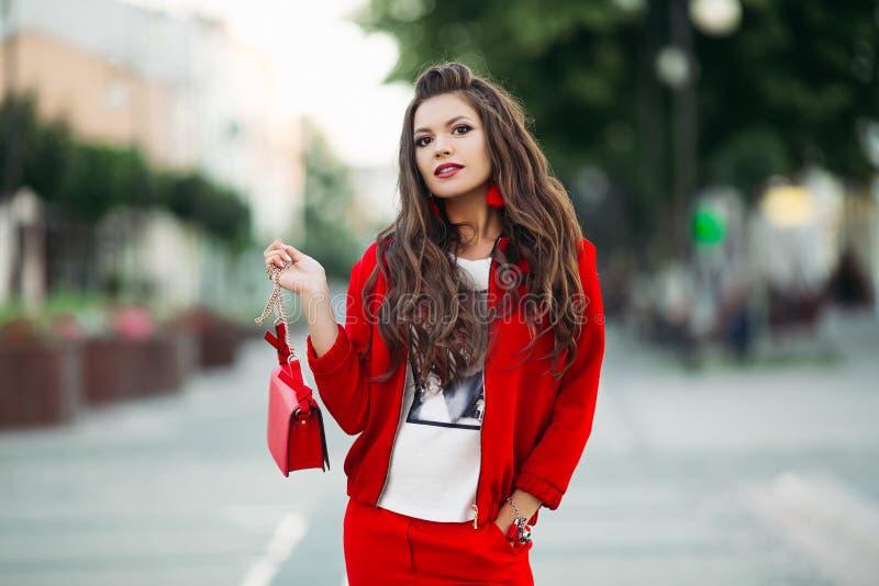 Модная девушка в костюме красного спорта шикарном с crossbody сумкой в th стоковое изображение