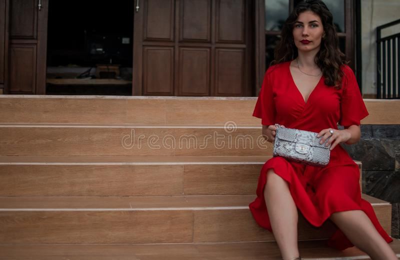 Модная девушка в красных drees держа кожаную сумку питона snakeskin, элегантное обмундирование Модель около дорогой виллы стоковое изображение rf