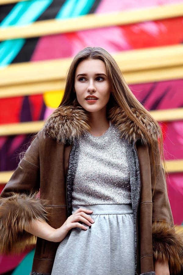 Модная длинн-с волосами девушка одетая в сером платье и длинном коричневом пальто овчины представляет в улице стоковые изображения rf