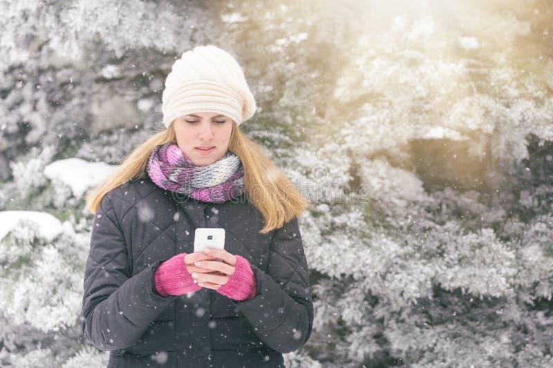 Модная женщина держа и смотря умный телефон alps покрыли древесины зимы малого снежка места дома швейцарские стоковое изображение