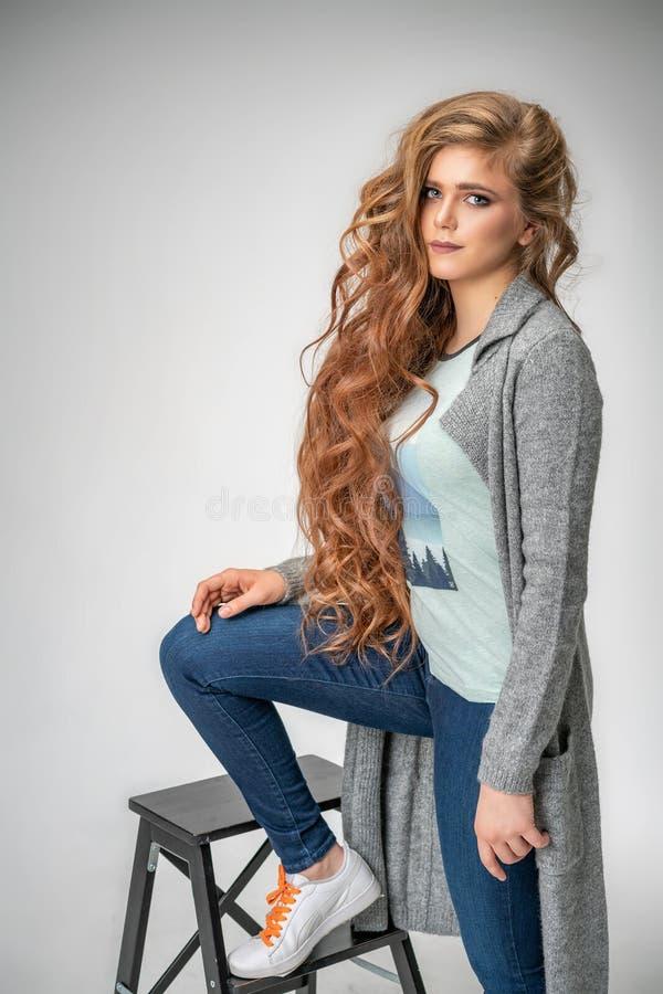 Модная женщина представляя на белой предпосылке, стильных джинсах оде стоковое фото rf