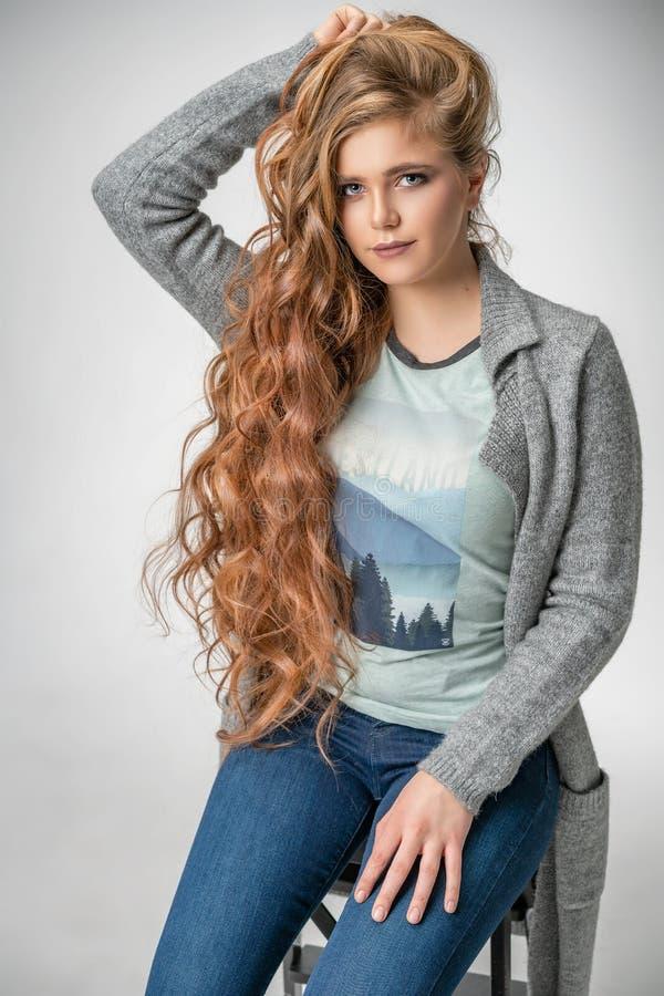 Модная женщина представляя на белой предпосылке, стильных джинсах оде стоковые изображения rf