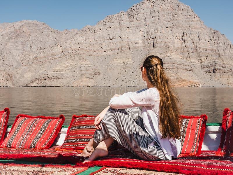 Модная женщина сидя в шлюпке Фьорды Омана стоковые изображения