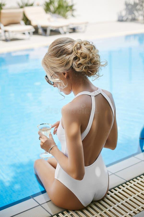 Модная и красивая модельная белокурая девушка с сексуальным телом в стильных солнечных очках и белом купальнике с нагой задней ча стоковые фотографии rf