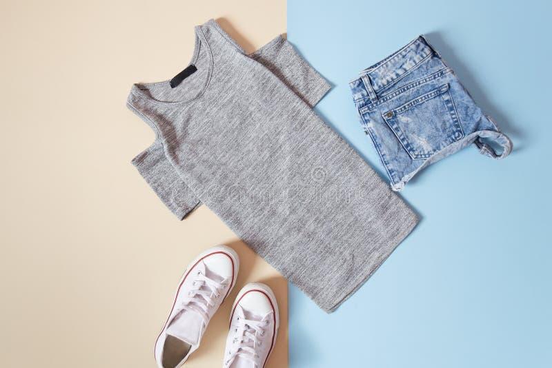 модная концепция Стиль ` s женщин городской Серая футболка, белые тапки и шорты джинсов на мягкой голубой предпосылке стоковое изображение