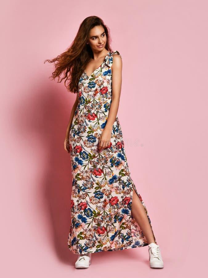 Модная красивая девушка брюнета в длинном зацветенном платье к полу и тапкам представляя на розовой предпосылке стоковые изображения