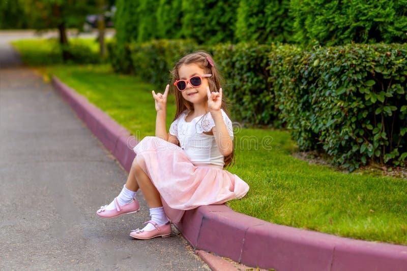 Модная маленькая девочка в солнечных очках на улице стоковые изображения