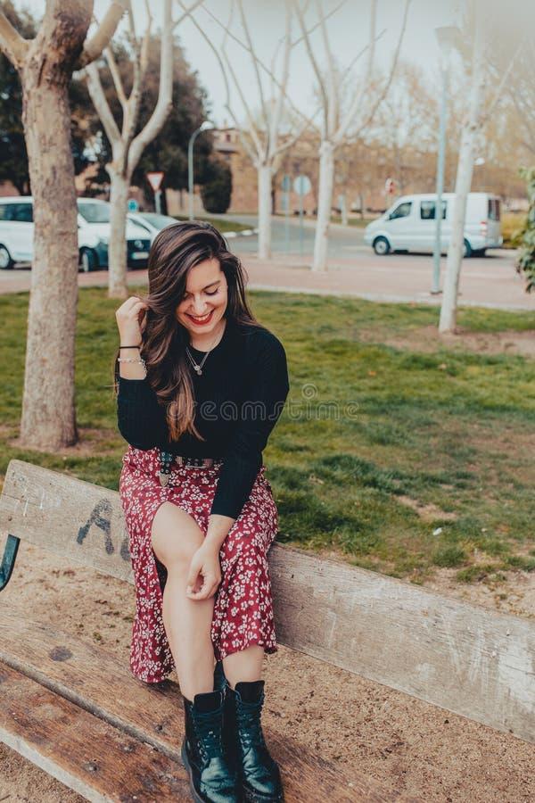 Модная маленькая девочка сидя на стенде смеясь застенчиво стоковое изображение rf