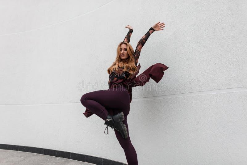 Модная милая молодая женщина с красными волосами в стильной блузке в ультрамодных брюках с пурпурной накидкой в черных танцах кож стоковая фотография rf