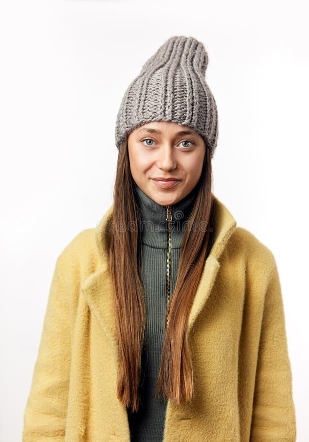 Модная модель женщины брюнета хипстера в стильной бежевой шинели и серой шляпе стоковое фото