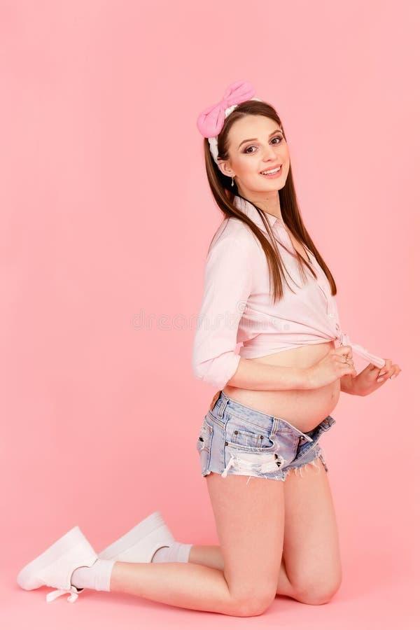 Модная молодая беременная девушка в студии на розовой предпосылке стоковые фото