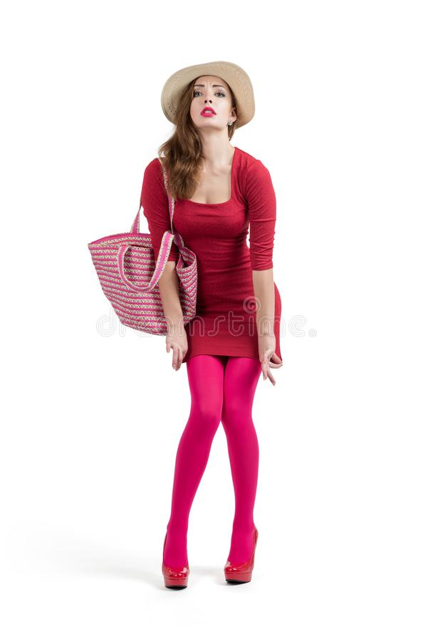 Модная молодая женщина в красных платье, шляпе и сумке, застенчивом белизна изолированная предпосылкой стоковая фотография rf