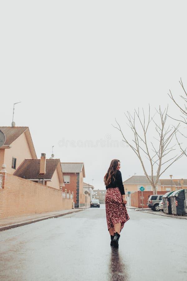 Модная молодая женщина идя и усмехаясь в дожде стоковые изображения