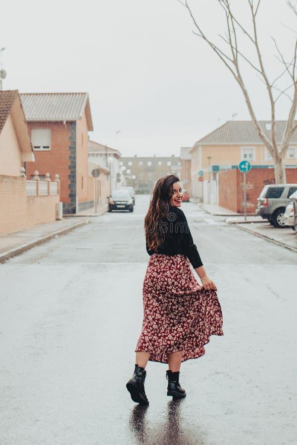 Модная молодая женщина моча ее юбку и усмехаясь в дожде с черными ботинками и напечатанной длинной юбкой стоковые фотографии rf