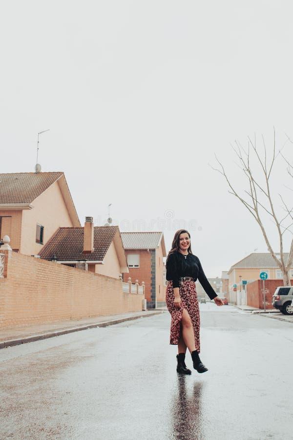 Модная молодая женщина скача в дождь стоковое изображение