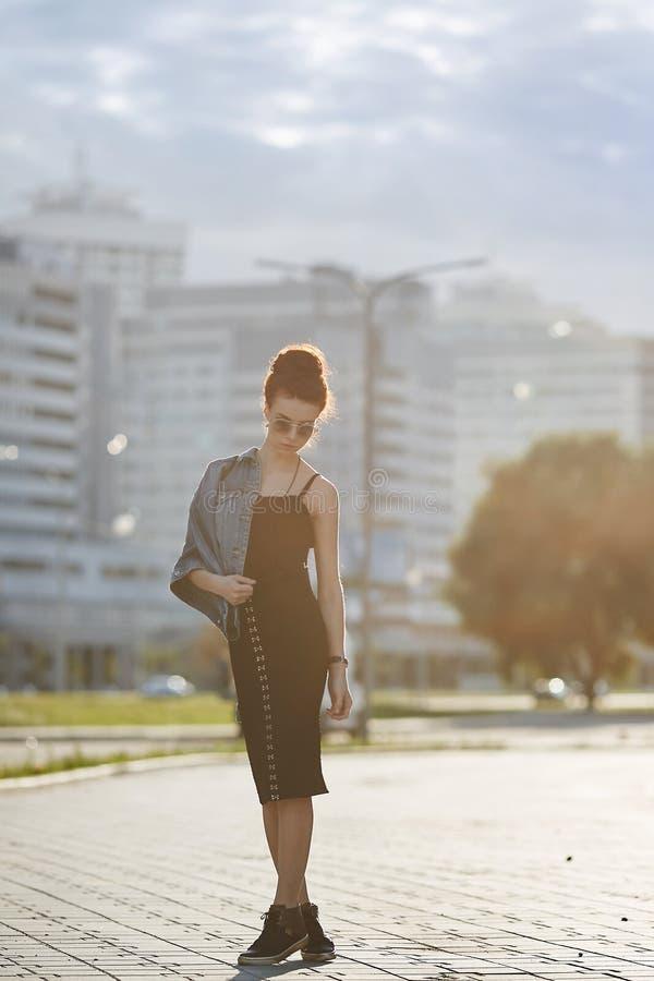 Модная, стильная и красивая молодая женщина брюнет в куртке джинсов, черное платье и тапки представляя outdoors на стоковые фотографии rf