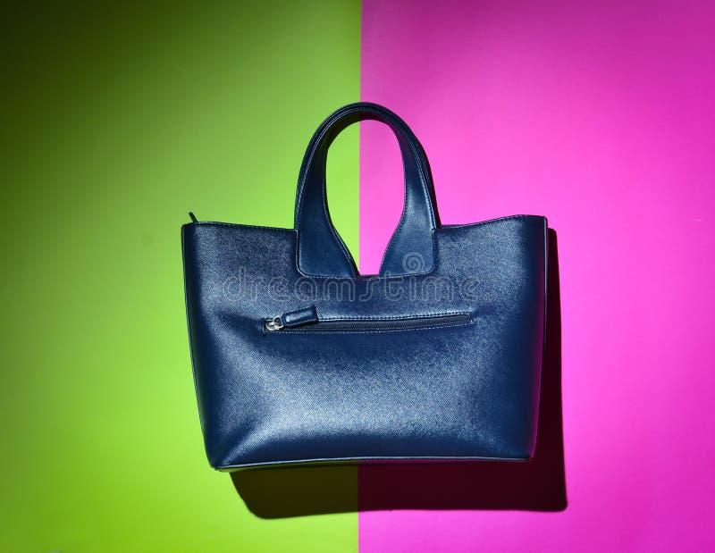 Модное women& x27; s кроет кожей сумку на зеленой розовой неоновой предпосылке стоковое изображение