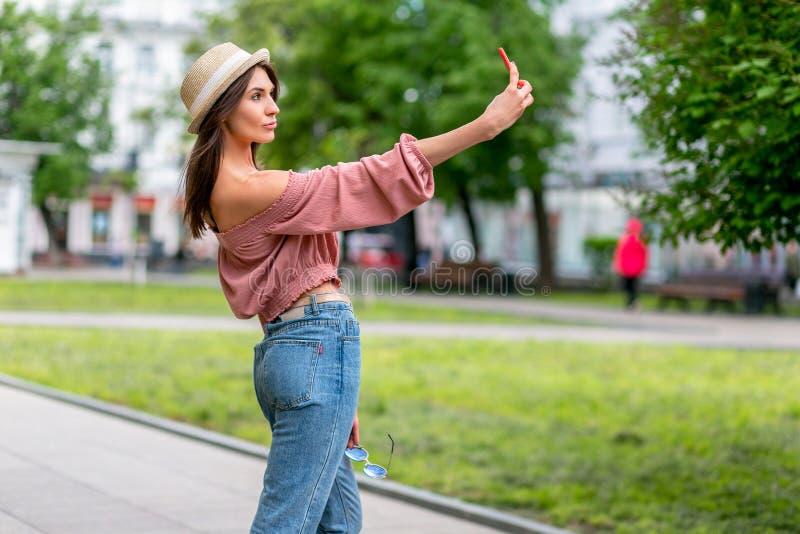 Модно одетая молодая женщина принимая selfie на улице на солнечном вечере Девушка в джинсах, блузке и небольшой шляпе смотрит стоковые изображения rf