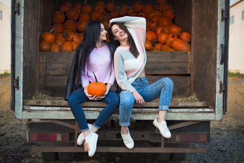 Модные красивые молодые девушки совместно на предпосылке заплаты тыквы осени Иметь потеху и представлять стоковое фото rf