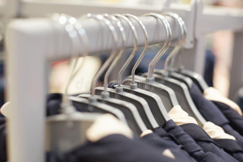 Модные одежды на вешалках в современном торговом центре Одежды хранят для женщин и людей Детали одежды в моле моды Fashio стоковое изображение rf