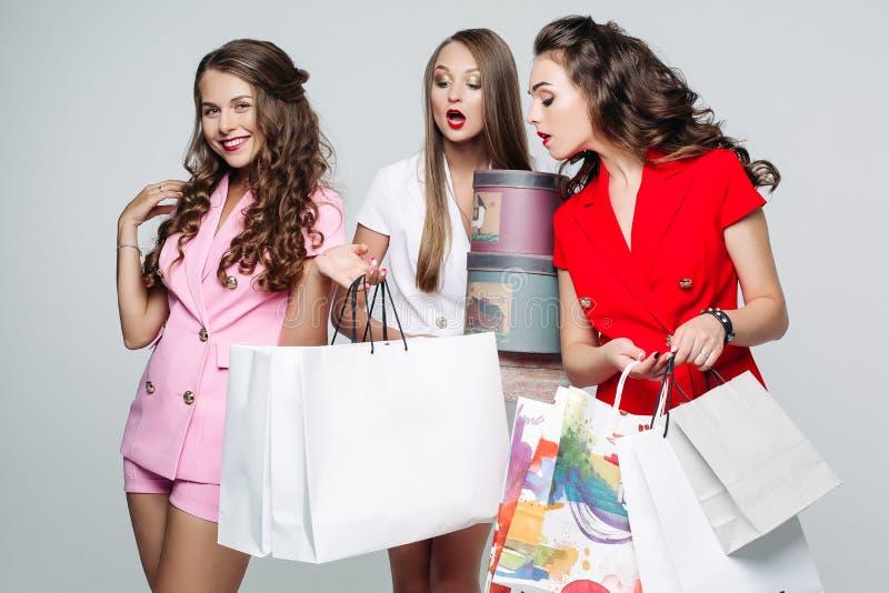 Модные подруги после ходя по магазинам удивленных смотря внутренних сумок стоковое фото rf