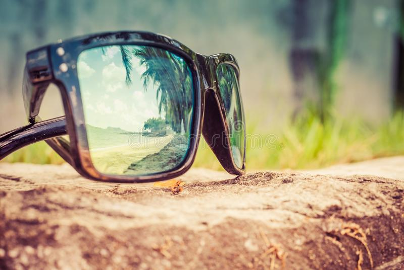 Модные солнечные очки Солнечные очки с отраженными объективами Отражение пляжа и тропических пальм в солнечных очках стоковые фото
