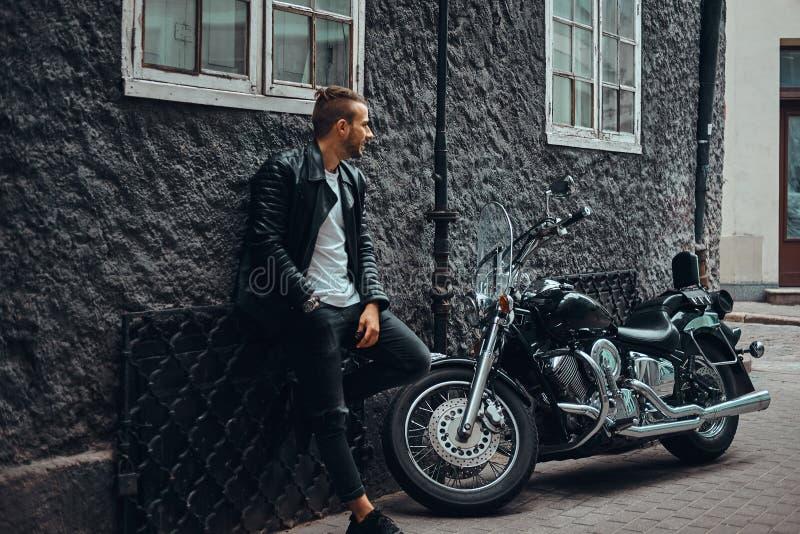 Модный велосипедист одел в черной кожаной куртке и джинсах полагаясь на стене около его ретро мотоцикла на старой Европе стоковая фотография rf