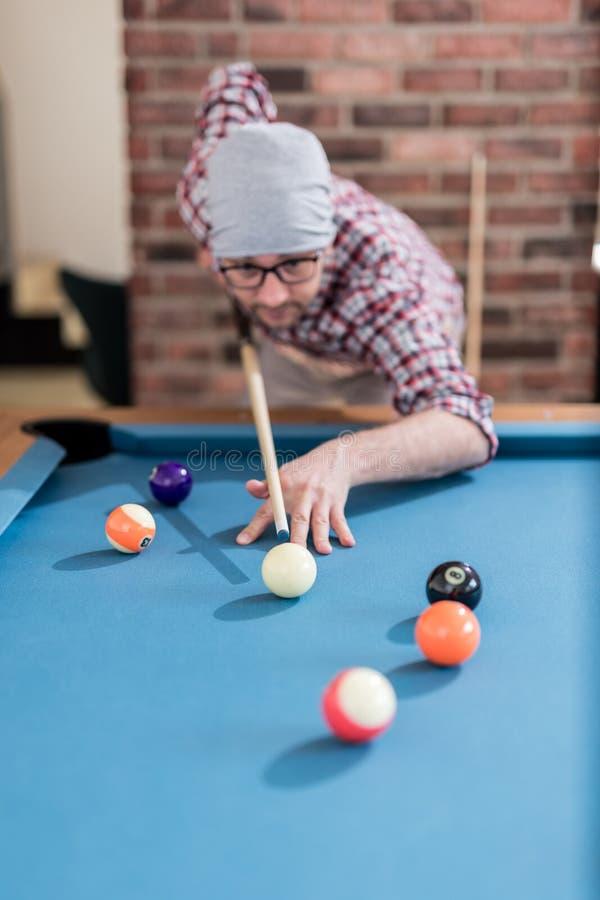 Модный городской человек играя игру билльярдов бильярдного стола стоковое фото rf