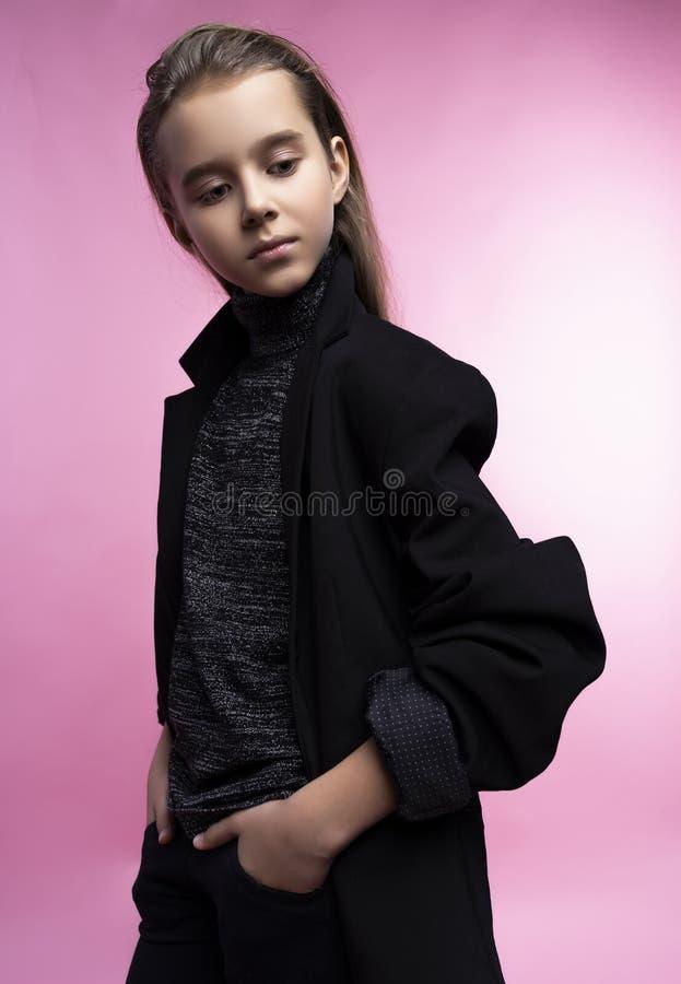 Модный портрет красивой милой предназначенной для подростков девушки нося серый turtleneck, джинсы и куртку блейзера Розовая пред стоковые фотографии rf
