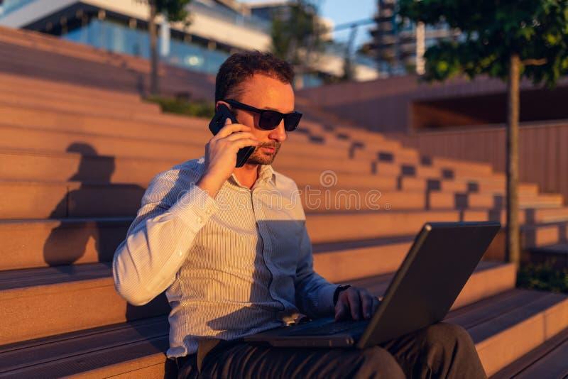 Модный фрилансер используя современную технологию и сидящ на лестницах стоковые изображения rf