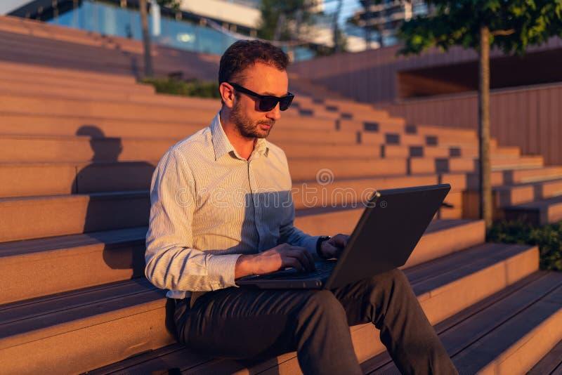 Модный фрилансер работая на ноутбуке и сидя на лестнице перед организацией бизнеса стоковые изображения