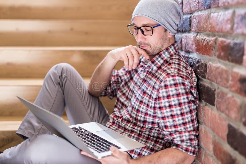 Модный фрилансер сидя на лестницах в офисном здании и смотря экран ноутбука стоковые фото