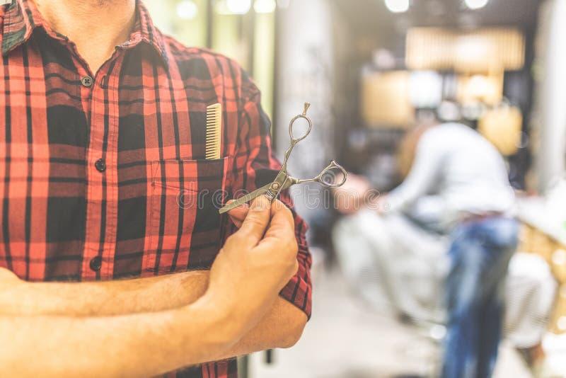 Модный человек держа ножницы перед парикмахерскаей r стоковые изображения rf