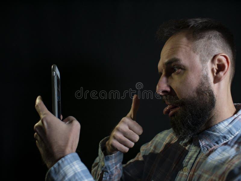 Модный человек с бородой и усиком гримасничает и принимает selfie по телефону на черной предпосылке стоковые фотографии rf