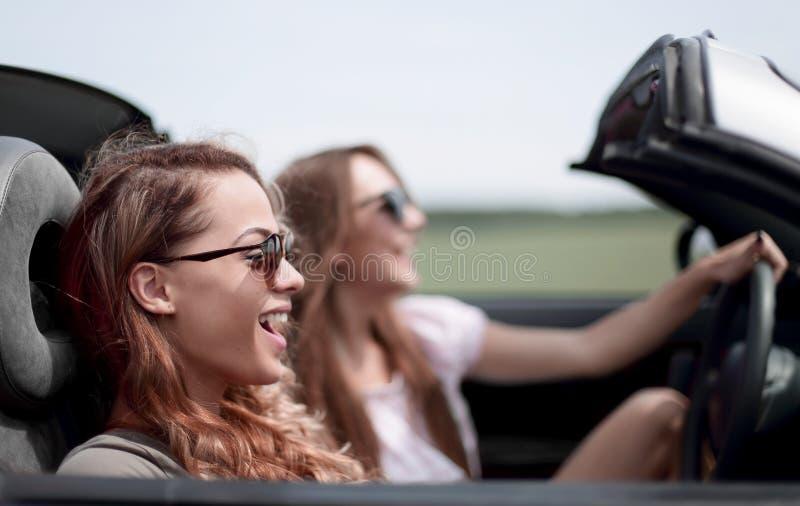 2 модных девушки путешествуют в обратимом автомобиле стоковые фотографии rf