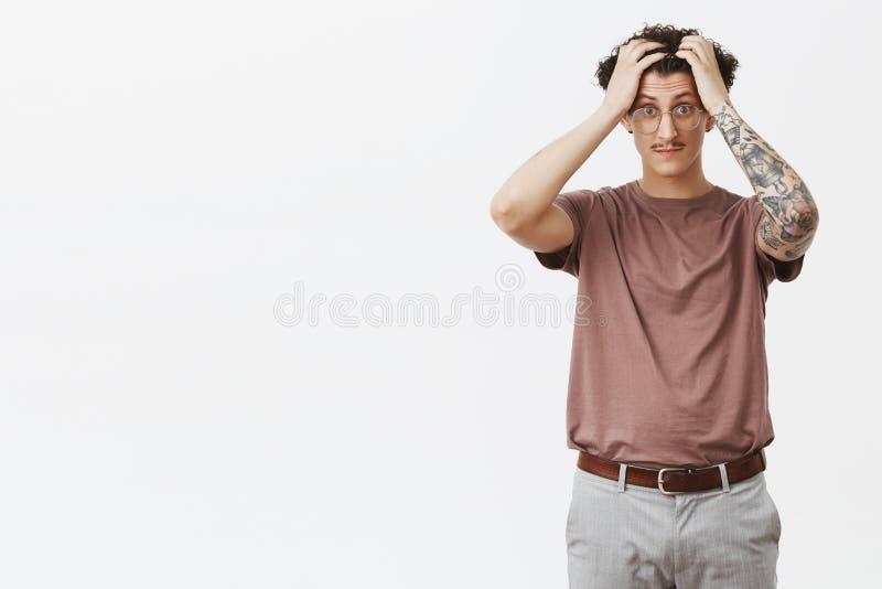 Мозги кипят от глупых студентов Портрет побеспокоенный и сотрясенный оглушил привлекательный молодой курчавый парня со смешным стоковые изображения rf