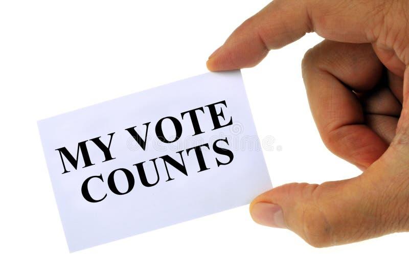 Мои отсчеты голосования написанные на держат карте, который в руке на белой предпосылке стоковое изображение rf